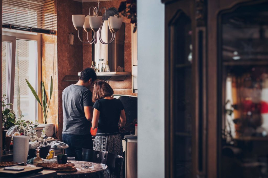 couple cooking together in kitchen with their backs turned