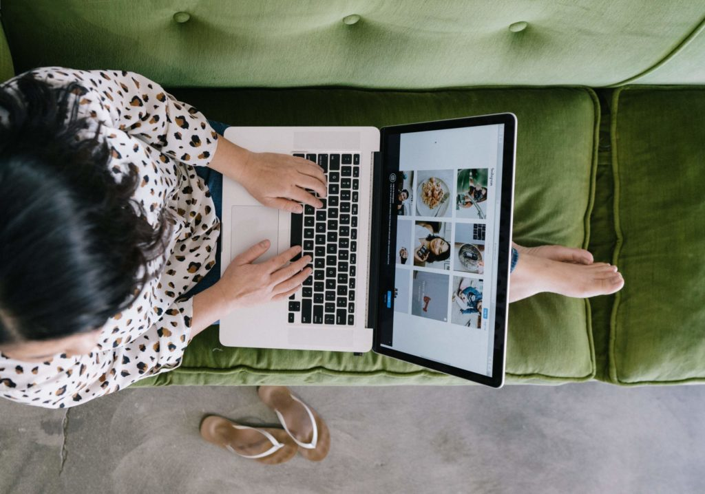 Woman sitting on green couch with laptop