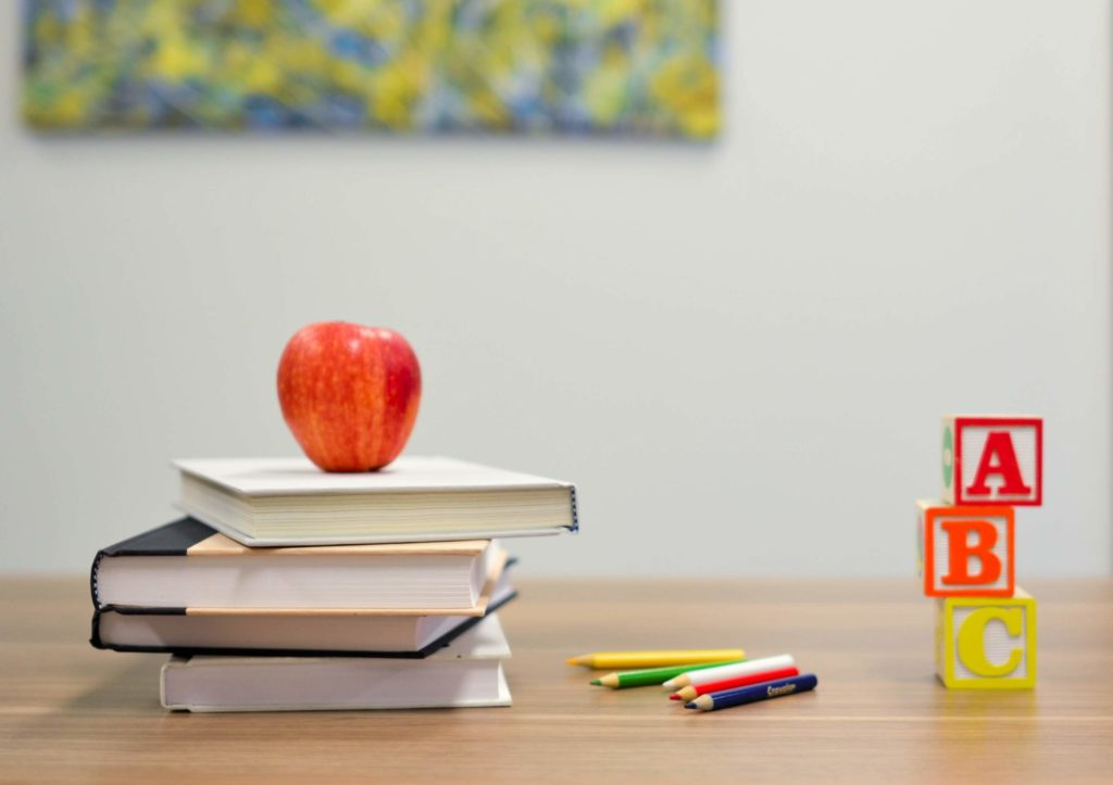 Red apple on top of school books
