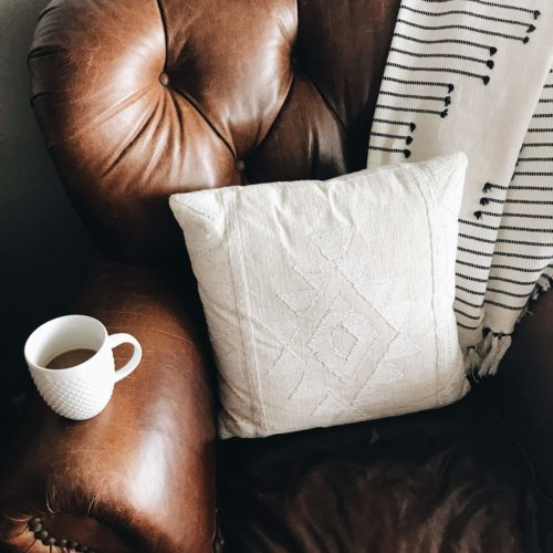 brown leather couch with coffee mug white pillow and blanket